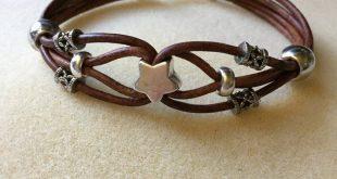 Dieses Armband ist aus Lederband und Silberperlen mit einer Schließe gefertigt.